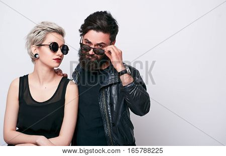 fashion couple in leather clothes posing in studio over white background. Young woman with short hairstyle and retro sunglasses leaning on her hipster bearded boyfriend wearing black leather jacket