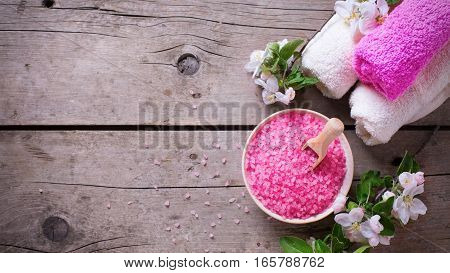 Spa or wellness organic product. Pink sea salt in bowl towels and flowers on aged wooden background. Selective focus. Place for text. Toned image.