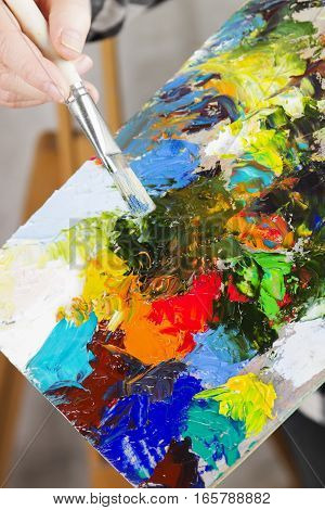 The Girl Artist Holds A Brush And A Wooden Palette With Various Art Oil Paints