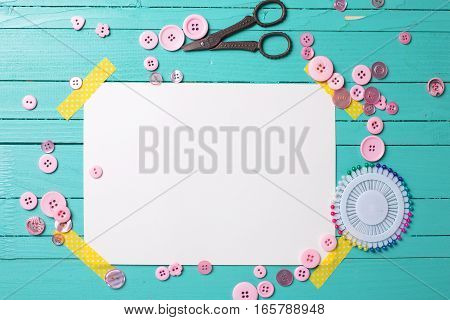 Sewing thread - buttons scissors and empty tag on turquoise wooden background. Selective focus. Scrapbboking. Flat lay. Place for text.