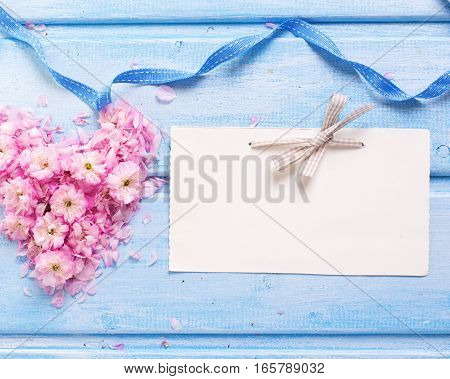 Background with heart from pink sakura flowers and empty tag on blue wooden planks. Selective focus. Place for text.