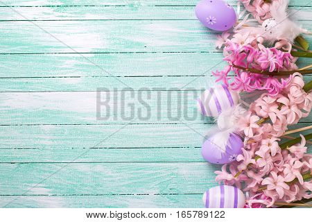 Easter or spring background. Border from decorative violet eggs and pink hyacinths flowers on turquoise wooden background. Selective focus. Place for text.