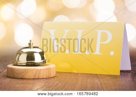 Close-up Of Service Bell With Vip Card On Wooden Desk