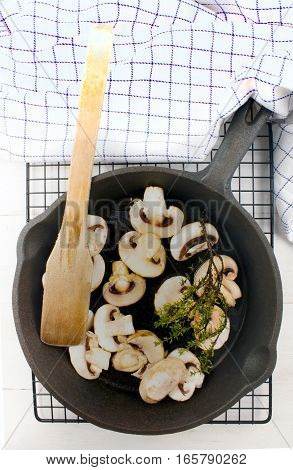 fresh mushroom with thyme in a cast iron pan