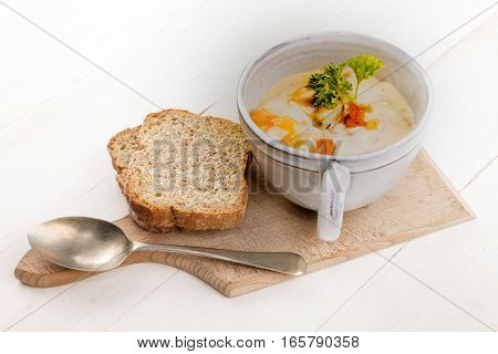 scottish fish soup in a cup and two slices of soda bread on a wooden board