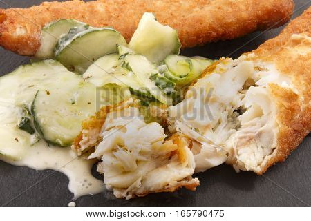 fried haddock and fresh cucumber salad with cream on slate