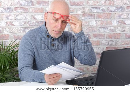 handsome mature man opening letter envelope in his office