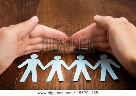 Close-up Of Person Hand Protecting Human Figure Cutout On Wooden Desk