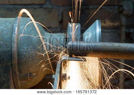 Worker using grinding wheel in workshop. Foto