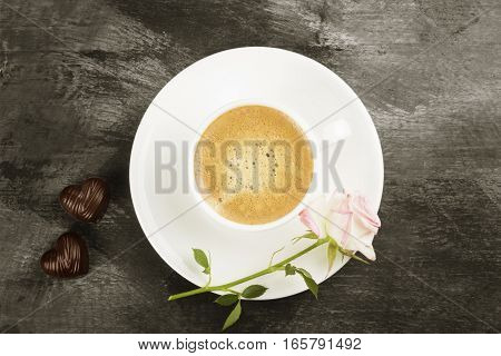 Espresso Coffee In A White Cup, A Pink Rose And Chocolates On A Dark Background. Top View. Food Back