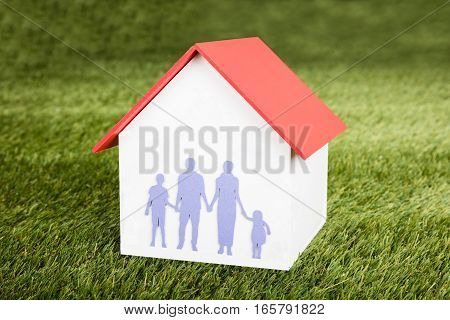 Close-up Of House Model With Family On It On Grassy Field