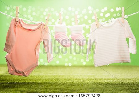 Baby Cloths And Baby Sock Hanging On Rope Using Wooden Clip