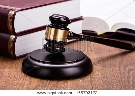 Law Gavel With Books On Wooden Desk In Courtroom
