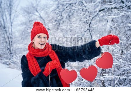 Love and valentines day concept. Happy excited woman holding garland of three red paper hearts shape - blank copy space for letters or text over winter landscape