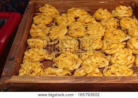 Uncooked Tagliatelle Italian Pasta In Wooden Box