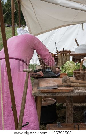 Woman with Pink Tunic preparing Black Pan for Cooking inside Tent