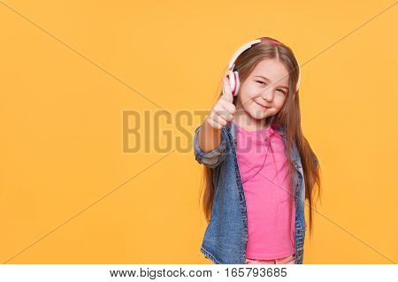 Portrait of stylish and cute little girl showing thumbs up isolated one yellow color background. Modern kid in headphones listens to the music with copyspace