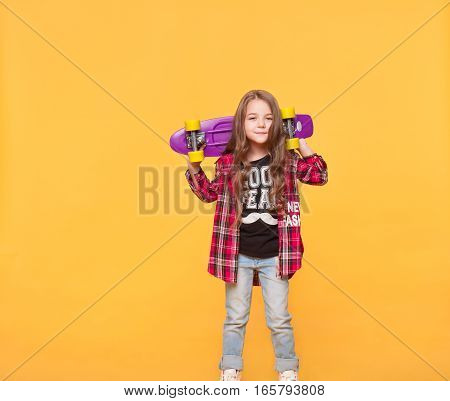 Full length cute little girl in casual hipster clothes isolated over yellow background. kid in jeans and checked shirt. Fashion child in trendy clothes holding skateboard