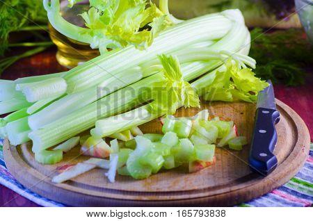 stalks of fresh celery on a kitchen wooden board