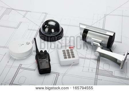 High Angle View Of Security Equipment On Blueprint In Office