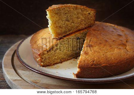 Homemade spiced banana sponge cake on wooden chopping board