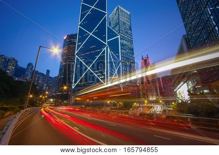 Business District Concept - Traffic trails on the Cityscape modern office buildings in central Hong Kong. Car light trails on city Skyline in downtown.