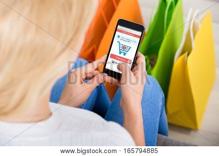 Close-up Of Young Woman Shopping Online Using Mobilephone With Shopping Bags On Floor