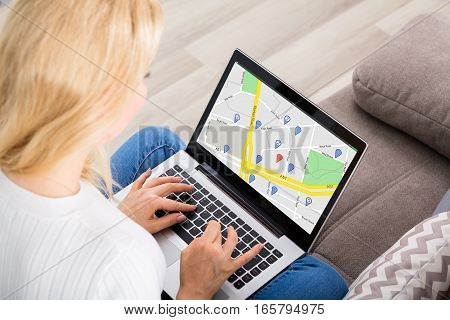 Close-up Of A Woman Using GPS Map With Navigation Pointers On Laptop