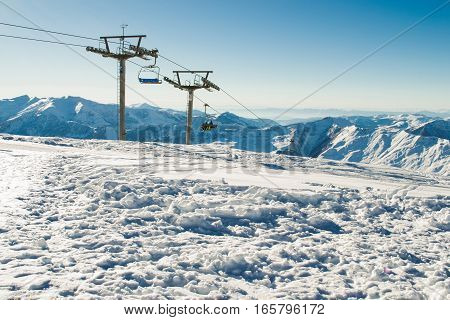 Photo of the View chairlift at ski resort with mountain range on background. Extreme sport. Active holiday. Free time, travel concept. Copy space