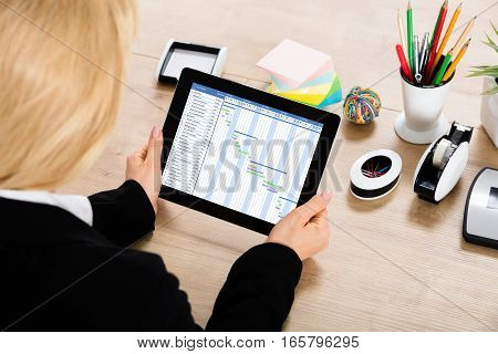 Close-up Of A Businesswoman Working On Gantt Chart On Digital Tablet On Office Desk