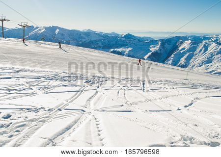 Photo of the Ski run with amazing view on Caucasus Mountain range. Skiing resort. Extreme sport. Active holiday. Free time, travel concept. Copy space