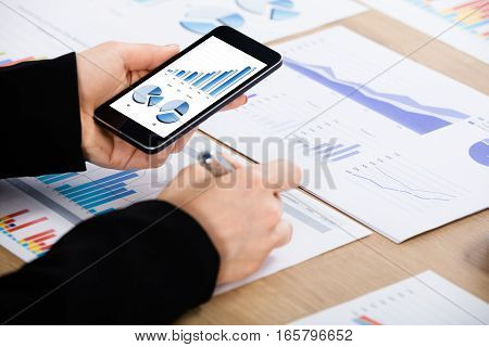 A Businesswoman Working On Financial Graph Using Mobilephone At Office Desk