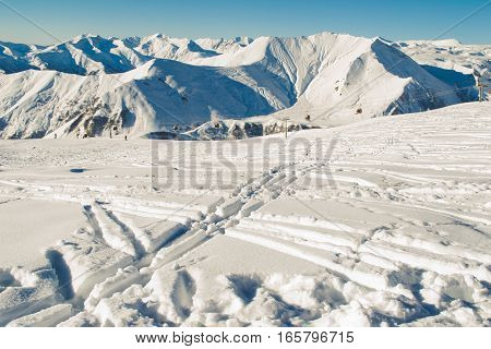 Photo of the Freeride concept. Ski traces on snow. Greater Caucasus Mountain Range in Georgia on background. Negative space for text. Extreme sport. Active holiday.