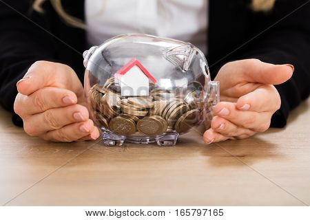 Businesswoman Protecting Her Savings With House Model In A Piggybank. Property Investment Concept