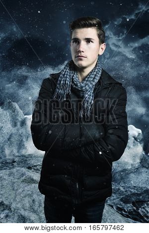 Serious boy with crossed arms in front of mountain and snowy landscape at winter season