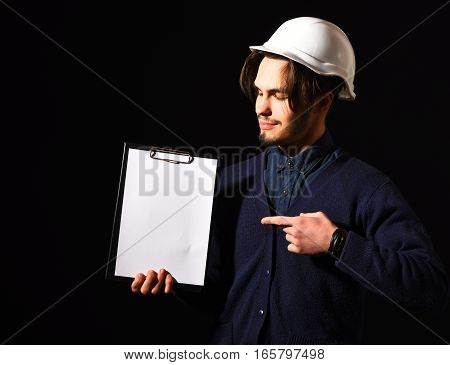 handsome bearded builder or foreman in blue sweater and helmet on smiling face holding tablet on black studio background copy space