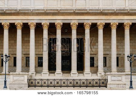 The front of a roman / greek resembling neoclassical style building with a line of corinthian ornate columns. Such a pillar collonade is typical for neoclassicism widely used in public buildings like government or education facilities, specially law court