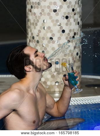 Handsome man muscular bearded hipster or sexy macho with muscle torso splashes water from mouth with cocktail in glass in pool indoors on blue mosaic background