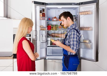 Young Woman Looking At Male Technician Checking Fridge With Digital Multimeter