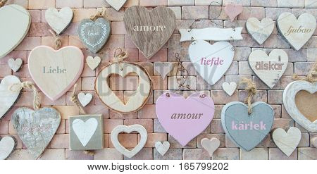 Variety of wooden hearts on a marbled stone background with love written in different languages