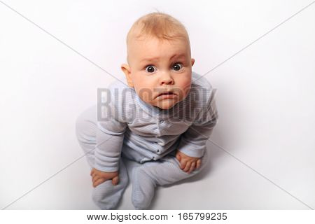 Baby sits in a blue dress on the bed