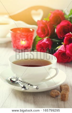 Valentine's Day: Romantic morning Tea Party for two with burning candles and bouquet of red roses. Toned image