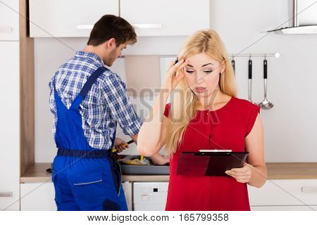 Young Frustrated Woman Looking At Huge Bill From Plumber Standing In Kitchen