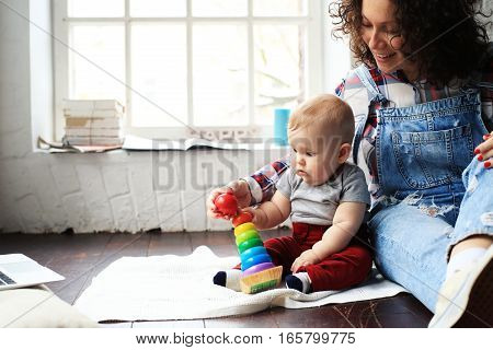 Mother and little child play in home