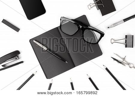 Blank notepad with clips, pens and glasses flat lay. Top view on set of black office supplies and spectacles on a white background, free space. Art, business, creation, imagination, education, stationery concept