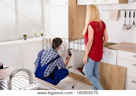 Male Worker Repairing Or Assembling Drawer Furniture With Young Woman Standing In Kitchen