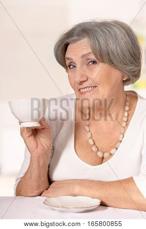 mature woman drinking coffee, close up portrait