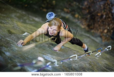 Woman Rock Climbing With Carbines And Rope