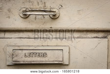 Old metal letter box r on an old wooden white door