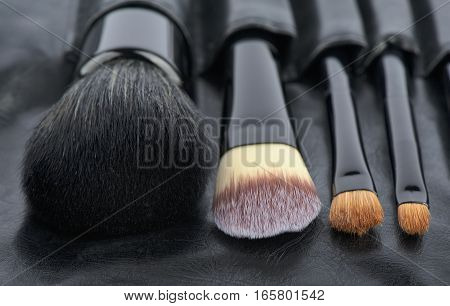 Brushes of Make-Up in a holder from leather